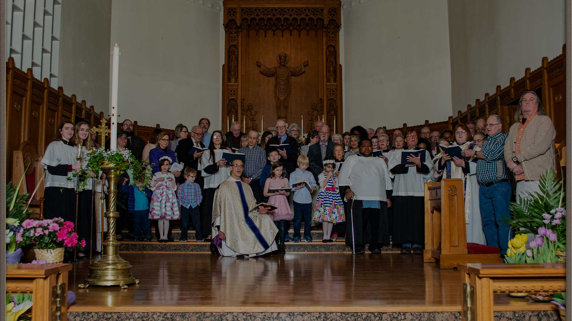 Members of the church standing at the altar singing.